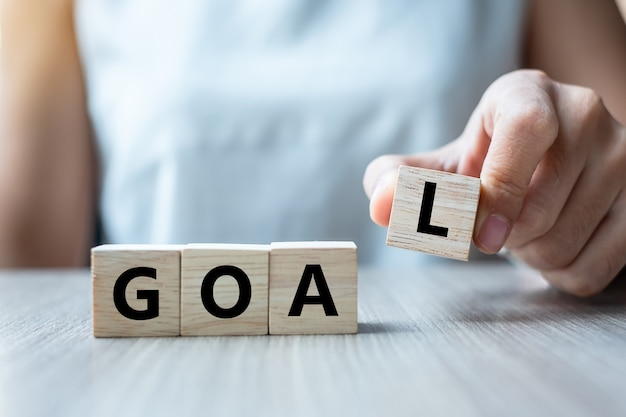 Holding wooden cube with goal text on table background.