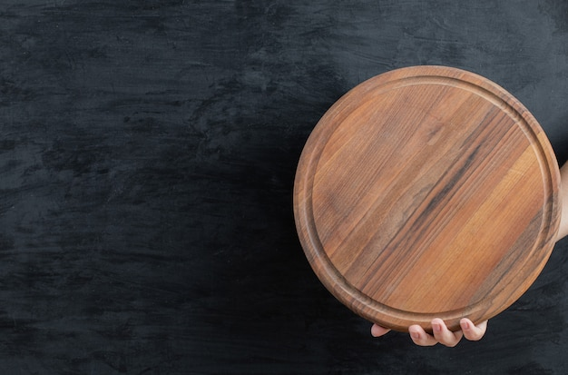 Tenendo in mano un piatto di legno su sfondo nero