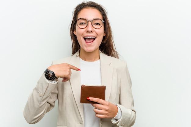 若いヨーロッパビジネス女性holdingwalletは、自分自身を指して驚いて、広く笑っています。