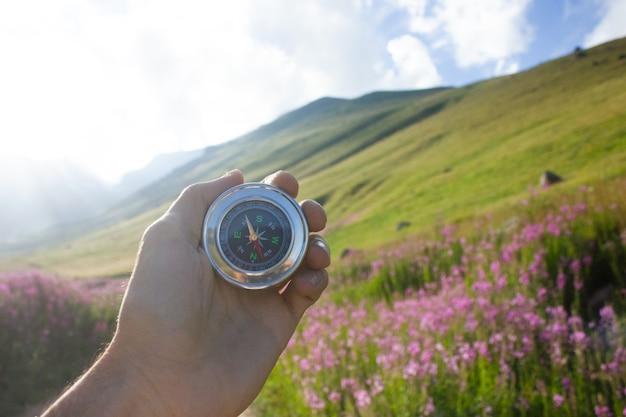 山と花の背景にコンパスを保持