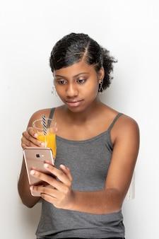 Держит стакан сока во время разговора по мобильному телефону