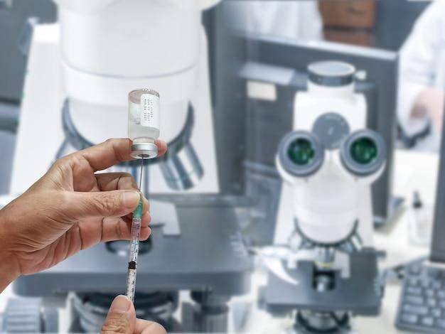 개발 실험실에서 액체 백신이 든 주사기를 들고 있습니다.