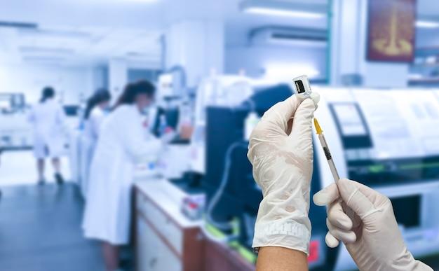 개발 실험실에서 액체 백신이 든 주사기를 들고 있습니다. 프리미엄 사진