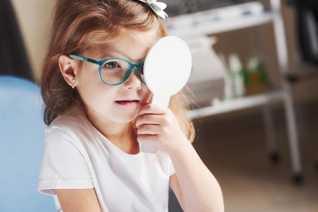 Удерживает окклюдер. маленькая девочка проверяет его зрение в новых зеленых очках.