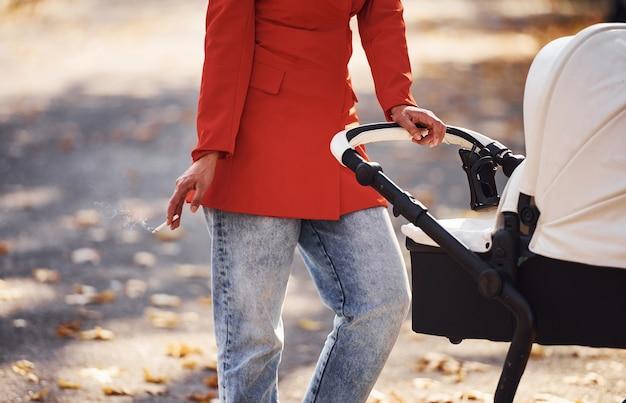 Держит сигарету в руке. мама в красном пальто и с сигаретой гуляет с ребенком в детской коляске в парке в осеннее время.