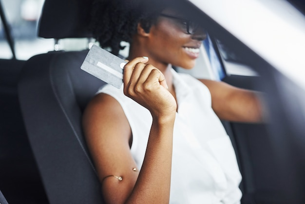 Holds credit card. young african american woman sits inside of new modern car.