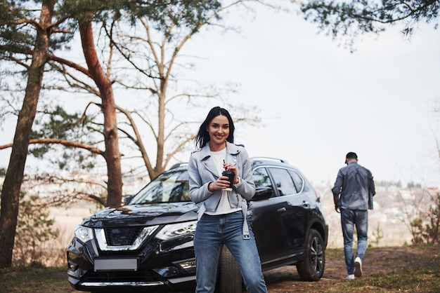 Holds cup with warm drink. couple have arrived to the forest on their brand new black car