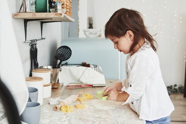 심장 모양의 악기를 보관합니다. 테이블 근처 부엌에 서서 밀가루로 노는 예쁜 소녀의 사진.