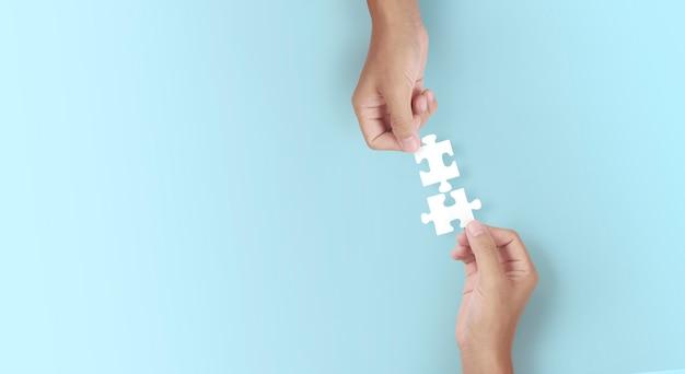 손에 직소 퍼즐을 쥐고 있습니다. 비즈니스 솔루션 성공 및 전략 개념