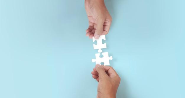 Держит в руке пазл. концепция успеха и стратегии бизнес-решений