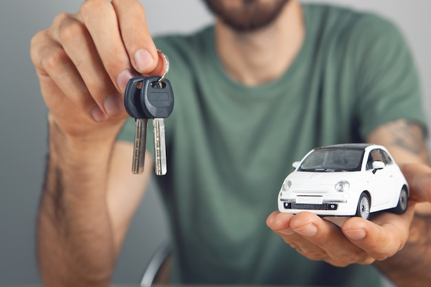 鍵と車を手に持つ