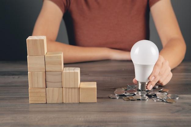 Holds a light bulb near a coin next to a ladder of cubes