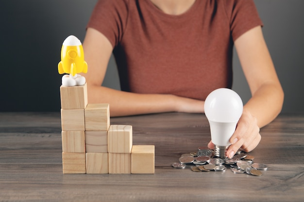Holds a light bulb near a coin and a rocket stands on a ladder of cubes