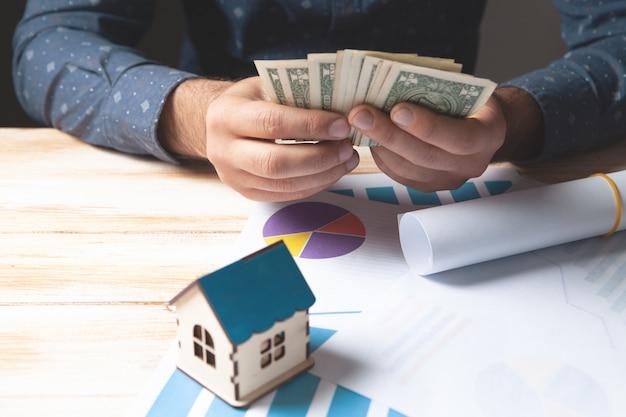Держит деньги перед бумагами и домом. концепция проекта дома
