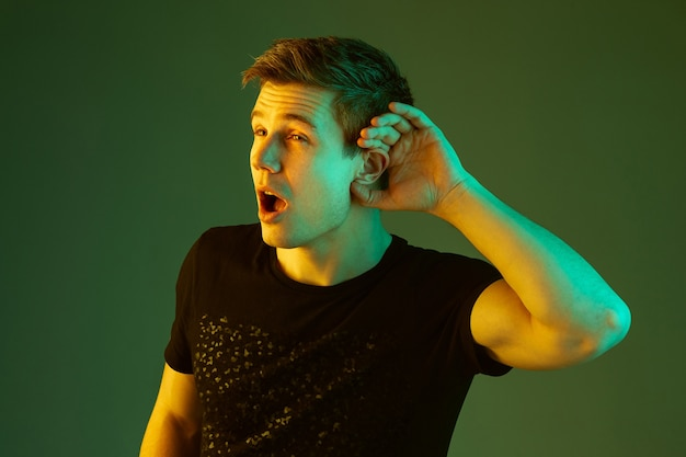 Holds palm on ear, listening. caucasian man's portrait isolated on green studio background in neon light. beautiful male model in black shirt. concept of human emotions, facial expression, sales, ad.