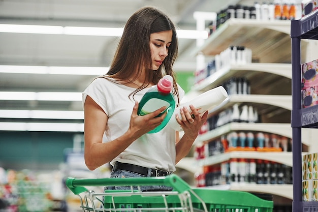 Holds product. female shopper in casual clothes in market.