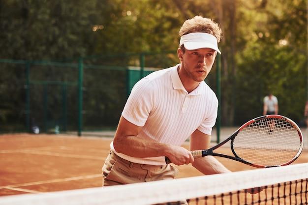ラケットを手に持ちます。スポーツ服を着た若いテニス選手が屋外のコートにいます。