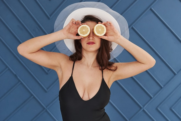 Holds sliced lemon in front of eyes. stylish beautiful young girl in bikini stands and posing