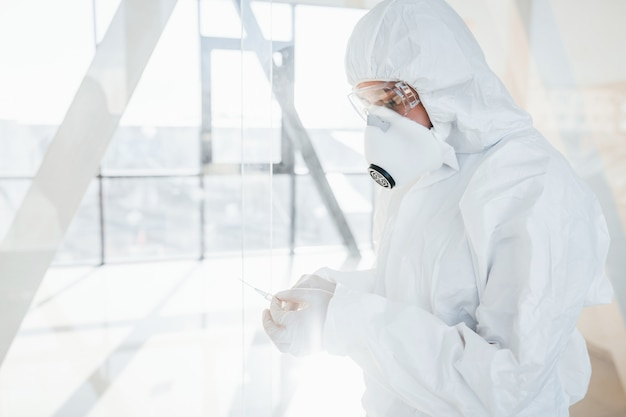Holds syringe with medicine. female doctor scientist in lab coat, defensive eyewear and mask standing indoors