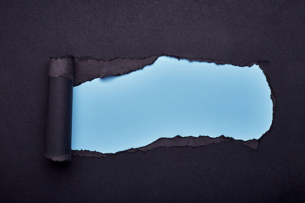 Hole in the black paper. torn. wooden . abstract .
