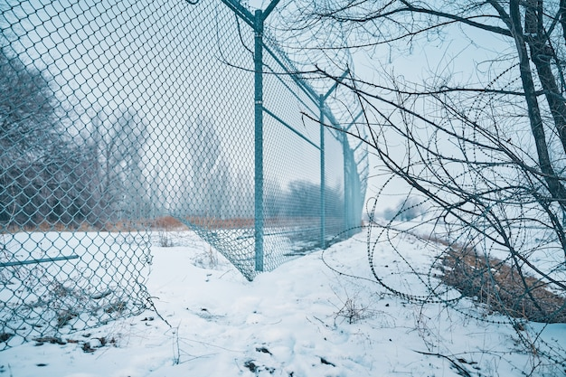 Hole in border fence with barbed wire escape from prison or closed institution for mentally ill unau...