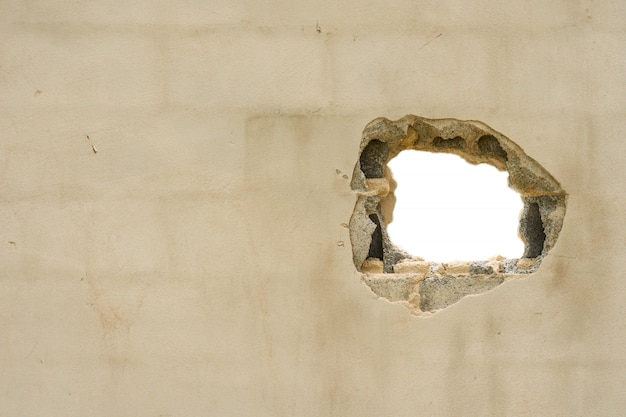 Hole in the concreate wall with white background and blank space