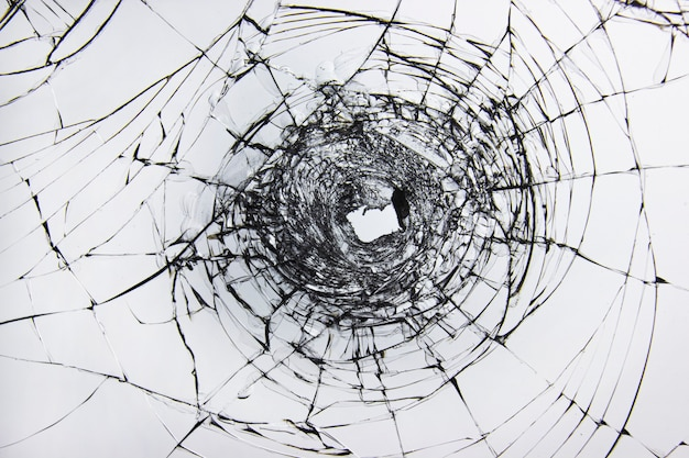 A hole and cracks in broken glass on a window of windscreen car glass. transparent windscreen of a car with a hole after the shots.