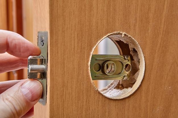 Отверстие для ручки в деревянной межкомнатной двери и латунная защелка.