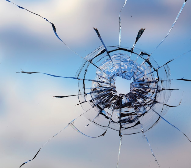 Hole from a bullet in the glass on a sky background