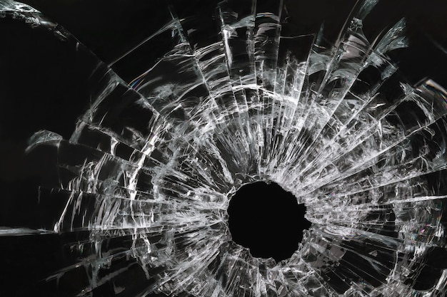 Hole in the glass from a bullet on a black background