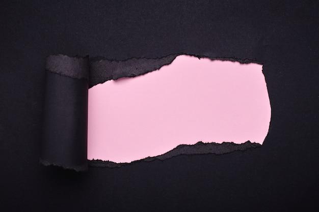 검은 종이에 구멍이 있습니다. 찢어진 분홍색 종이. 요약 .