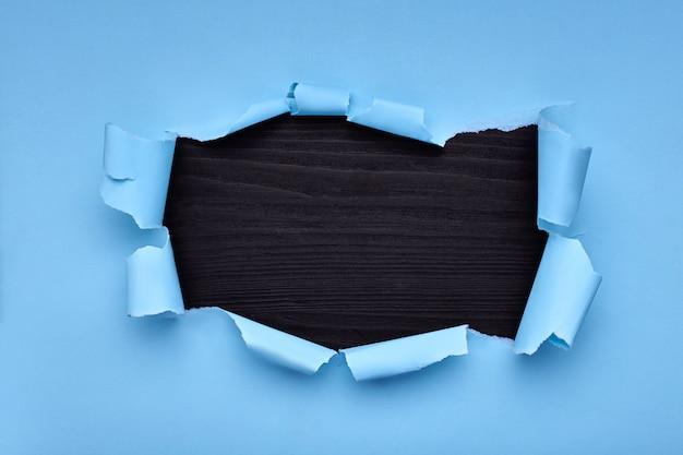 Дыра в синей бумаге. torn. черный деревянный. абстрактный