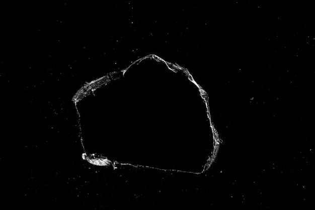 黒い背景に分離された亀裂のあるガラスの穴。デザインの質感