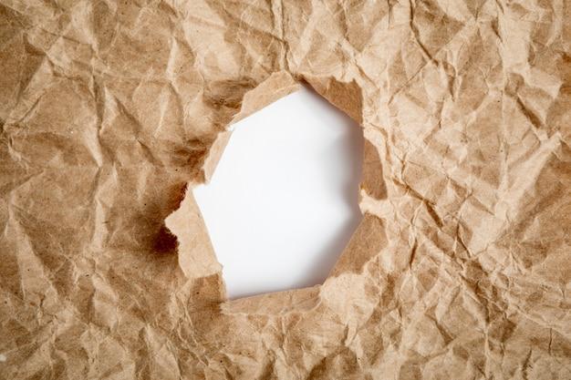 Отверстие в бумаге с рваными сторонами фона