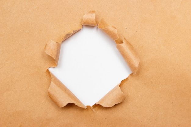 Hole into brown craft paper sheet with torn edges.