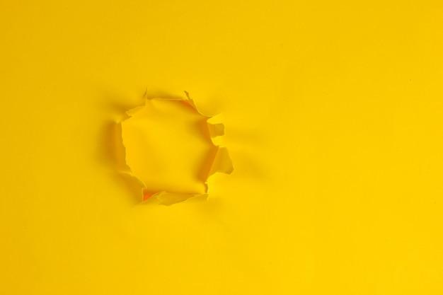 찢어진 된 노란 종이의 구멍입니다. 공간 복사