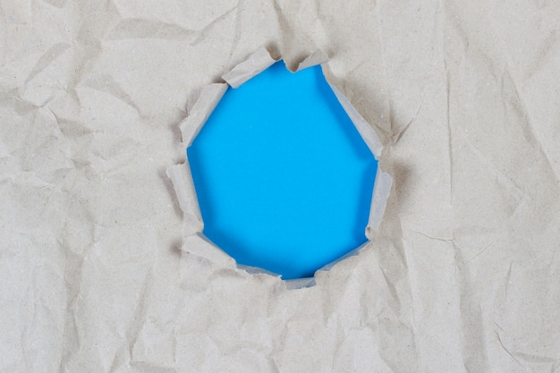 Hole in old crumpled paper with light blue background inside