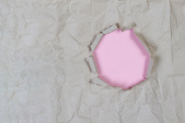 Hole in old crumpled paper with light pink background inside