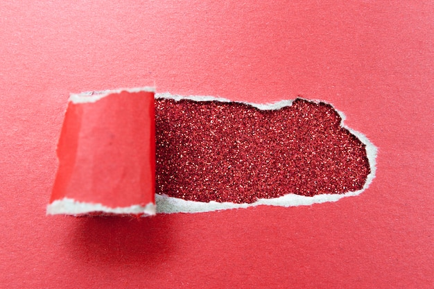 Hole in a sheet of red paper on a glittery surface