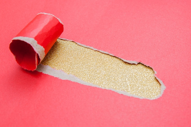 Hole in a sheet of red paper on a gold glitter surface