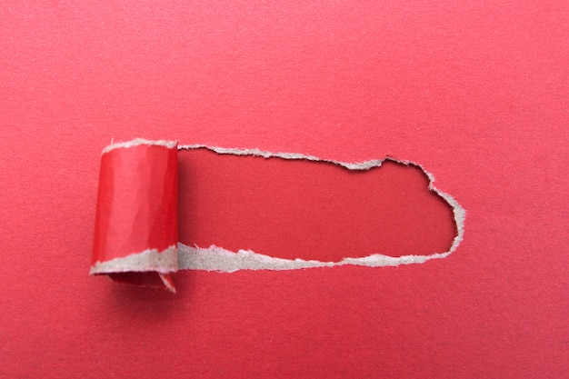 Hole in a sheet of red paper on a red surface
