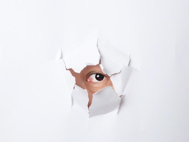 사람의 눈으로 종이에 찢어진 구멍