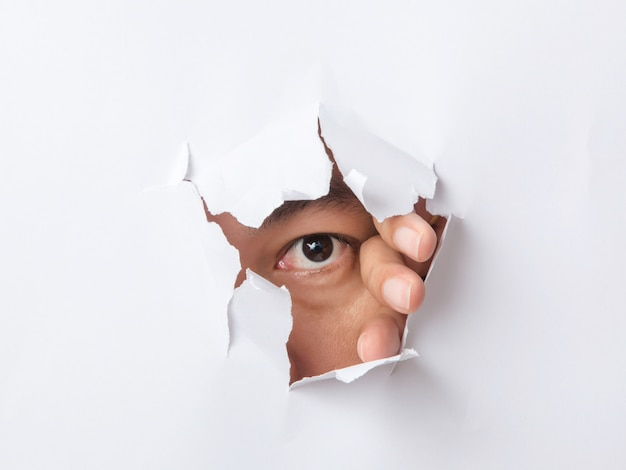 Hole torn in paper with the eye of man