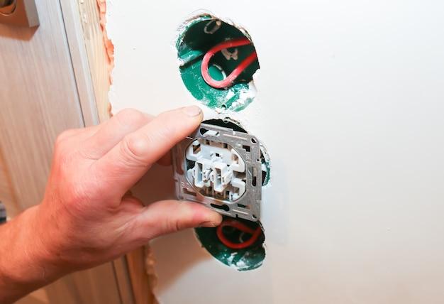 소켓 스위치용 컬러 와이어가 있는 벽의 구멍. 전기를 설치하는 남자. 유지 보수 수리는 아파트에서 보수 작업을 합니다. 실내복원.