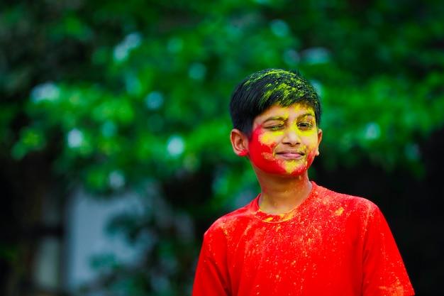 Празднование холи - индийский маленький мальчик играет на холи и показывает выражение лица.