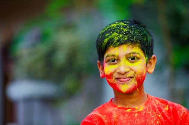 Holi celebrations -indian little boy playing holi and showing face expression.