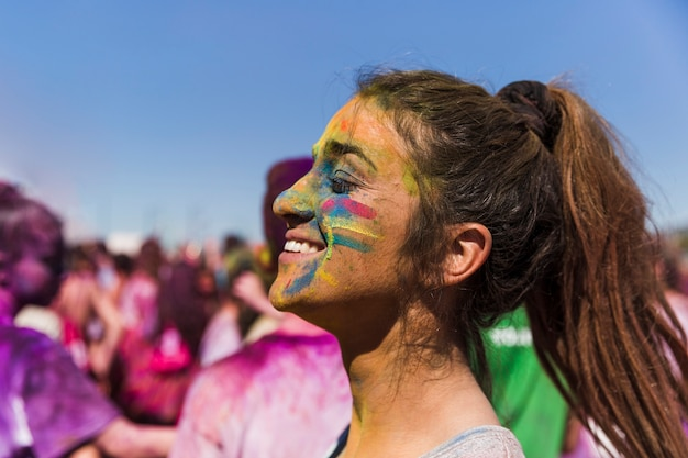 Holi color on woman's face in front of crowd
