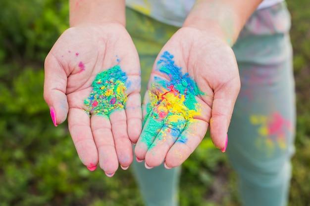 Фестиваль холи и концепция цвета - руки с желтым, синим, зеленым цветами.