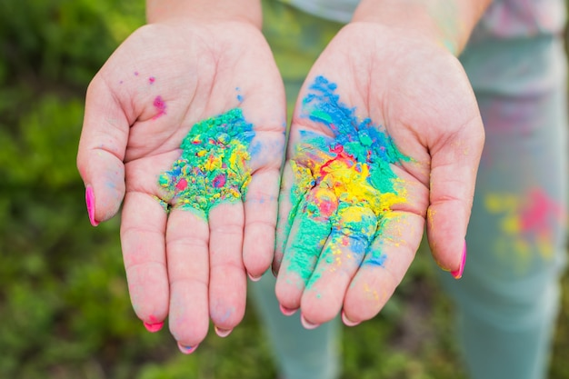 Holi festival and color concept - hands with yellow, blue, green colours.