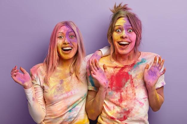 Festival di holi, divertimento e concetto di persone. due donne felicissime giocano con i colori, mostrano le palme, imbrattate di polvere colorata, isolate su un muro viola. esplosione multicolore